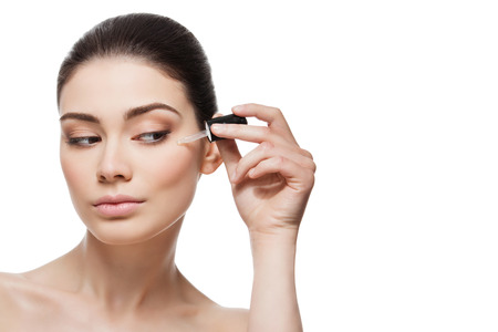 mujer maquillandose: Mujer joven hermosa que aplica el suero hidratante anti-edad a menos de área de los ojos. Aislado sobre fondo blanco. Copiar el espacio. Foto de archivo