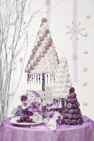 Beautiful set of three croquembouch macaron wedding cakes together with bridal bouquet and glass on table over snowy background
