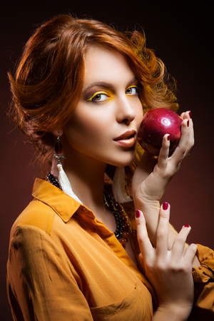 color model: Beautiful young woman with bright yellow makeup dressed in orange autumn style holding red apple