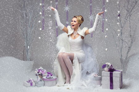 winter gift: Beautiful happy young bride in felted wedding gown throwing up snow. Present boxes decorated with purple flowers.