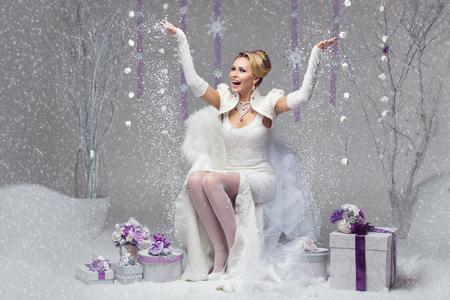 navidad elegante: joven y bella novia feliz en el vestido de novia de fieltro lanza para arriba nieve. los actuales cajas decoradas con flores de color púrpura.
