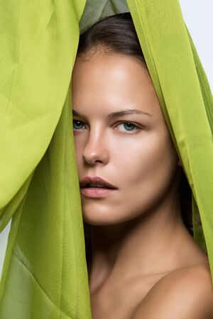 tratment: Closeup portrait of beautiful young woman covered with green textile. No makeup. Stock Photo