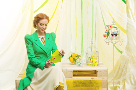envelope decoration: Beautiful young woman in yellow dress and green fashion jacket opening wedding present envelope. Decorated background.