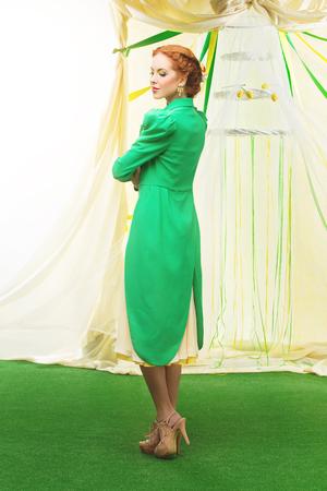 cola mujer: Joven y bella mujer con maquillaje en vestido amarillo y frac verde. Arco de la boda en el fondo. Copiar el espacio.