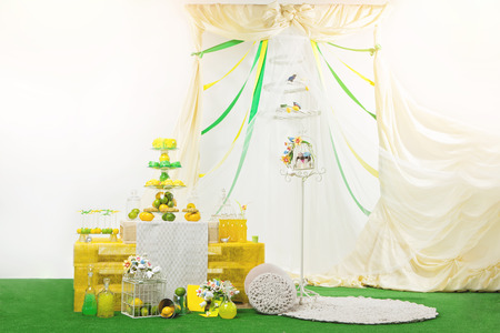 candy stick: Beautiful hand made dessert table with cake, muffins and ice pop. Decorated with bottles, cages, flowers and fruits. Wedding arch with textile and ribbons. Copy space.