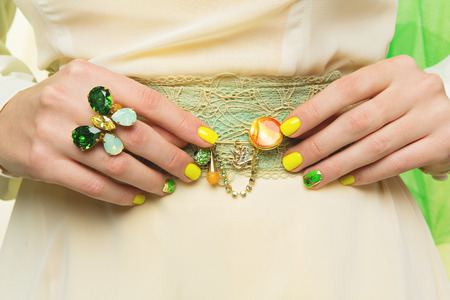 nailart: Closeup shot of woman hands with ring and yellow, green manicure holding brooch on belt Stock Photo