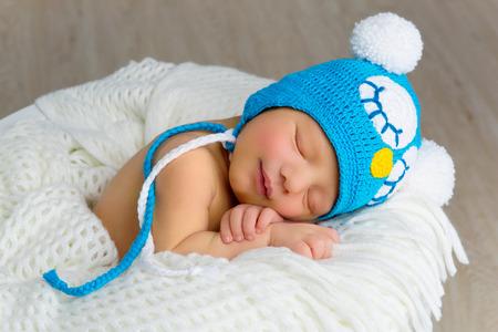 recien nacido: Feliz adorable bebé recién nacido que duerme en cesta blanco. Composición horizontal.