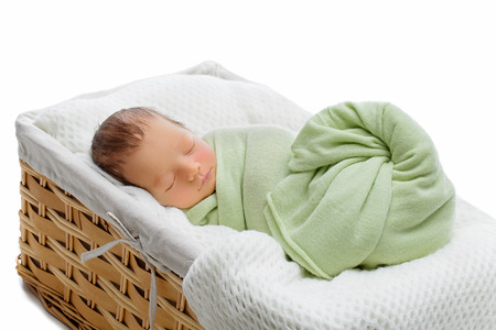 newborn: Adorable newborn baby boy sleeping in basket. Copy space. Horizontal composition. Isolated over white background. Stock Photo