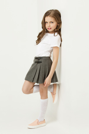 uniforms: Beautiful little girl in skirt standing near white wall and posing like model