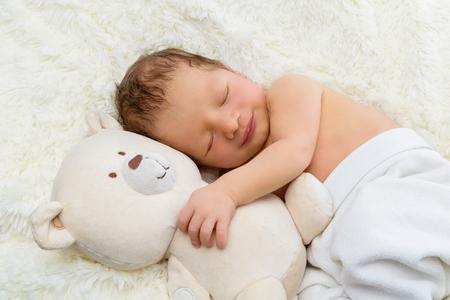 newborn animal: Adorable sleeping newborn baby boy hugging toy teddy bear