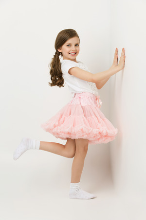 kid portrait: Beautiful little happy girl in tutu skirt standing near white wall Stock Photo