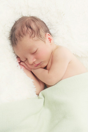 sleep baby: Adorable sleeping newborn baby boy with hands under head. Copy space. Vertical composition. Stock Photo