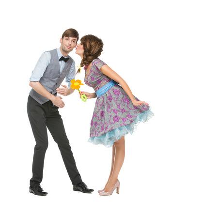 pareja saludable: Pareja joven hermosa que mira como muñecos de pie con la flor del juguete.