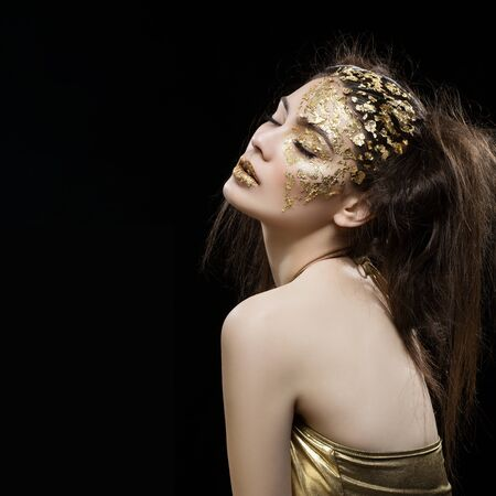 vogue style: Beautiful young woman with art golden foil makeup on face and lips. Square composition. Copy space. Over black background.