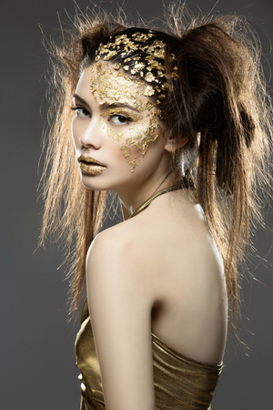 Beautiful young woman in dress with art golden foil makeup on face and lips. Over grey background.