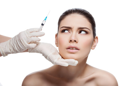 Scared young woman looking with fear at syringe. Beauty injection. Isolated over white background.