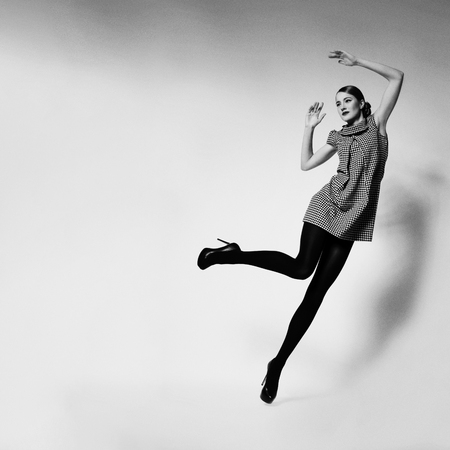 Beautiful slim young woman dressed in retro style falling to the side. Square composition. Copy space. Monochrome.
