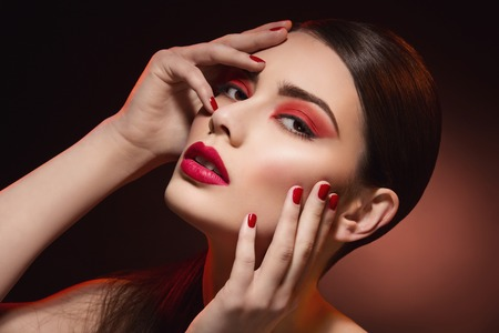 glamour model: Closeup portrait of beautiful young woman with bright red eyeshadows, lips and nails