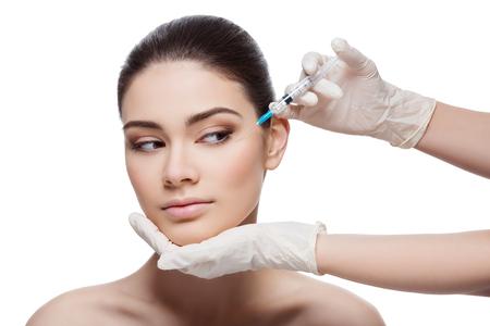 Piękna młoda kobieta dostaje zastrzyk kosmetyczny w okolicach oczu od sierżanta. Pojedynczo na białym tle.