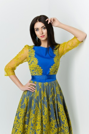 femme brune sexy: Beautiful young woman in festive blue dress with yellow lace standing near white wall