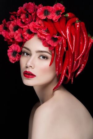 Closeup portrait of beautiful young woman with chilli peppers and flowers on head. Red lips.