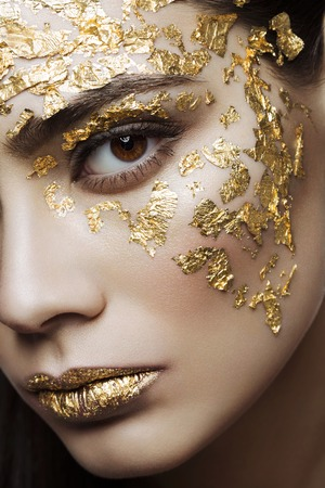 Closeup portrait of beautiful young woman with golden foil on face and lips. Creative makeup. Long hair Stock Photo