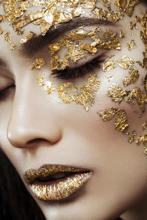 Closeup portrait of beautiful young woman with golden foil on face and lips. Creative makeup. Long hair Standard-Bild