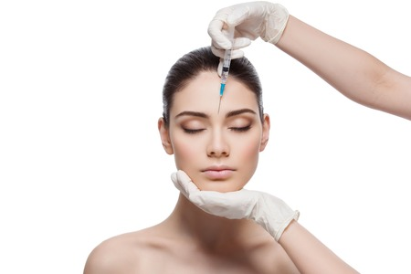 Beautiful young woman gets beauty injection in forehead from sergeant. Isolated over white background. Stock Photo