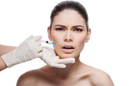 Mooie jonge vrouw met een uitdrukking van pijn op het gezicht krijgt injectie in de lippen van sergeant. Geïsoleerde over witte achtergrond.
