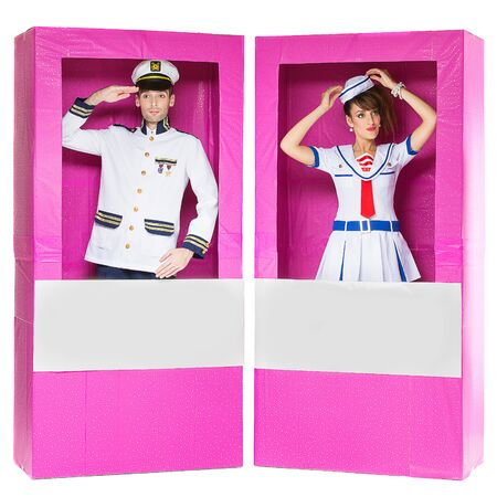 men standing: Hansome man and beautiful yung woman looking like dolls standing in pink boxes Stock Photo