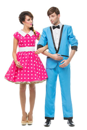 men standing: Beautiful fashionably dressed couple looking like dolls. Isolated over white background.