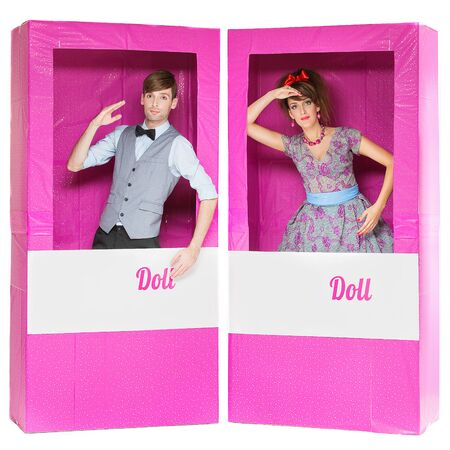 hansome: Hansome man and beautiful yung woman looking like dolls standing in pink boxes Stock Photo
