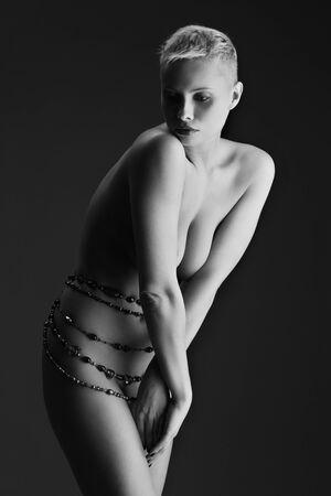 donna completamente nuda: Bella giovane donna nuda con perline in vita su sfondo scuro