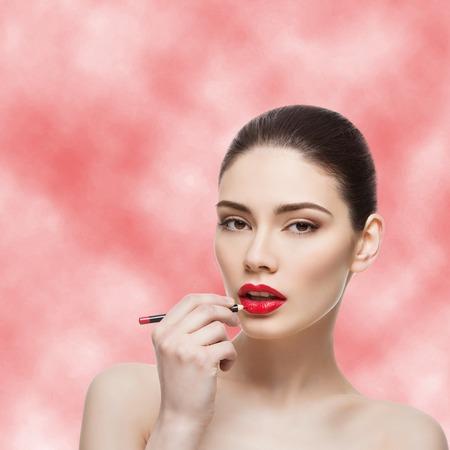 lip pencil: Beautiful young woman applying lip pencil. Over red smokey background. Beauty shot.