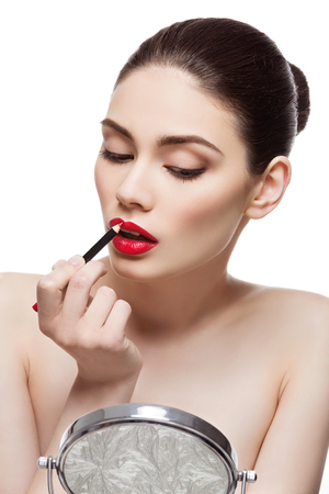 lip pencil: Beautiful young woman applying red lip pencil. Isolated over white background. Beauty shot.