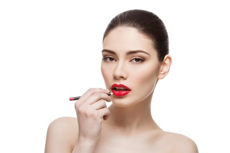 Beautiful young woman applying red lip pencil. Isolated over white background. Beauty shot.