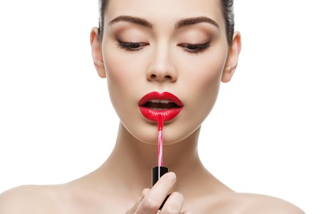 Beautiful young woman applying red lipgloss with applicator. Isolated over white background. Copy space. Reklamní fotografie