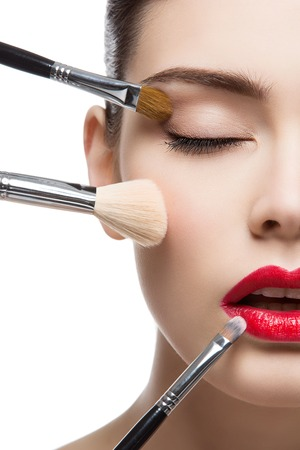 Closeup portrait of beautiful young woman with makeup brushes. Red lips. Isolated over white background.