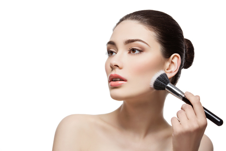skintone: Beautiful young woman applying face powder with dual fiber brush. Isolated over white background. Copy space.