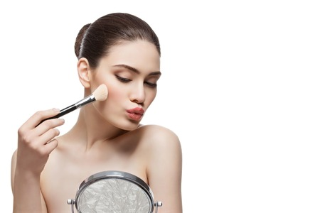 Beautiful young woman applying blush with brush and looking into table mirror. Isolated over white background. Copy space.