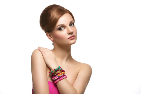 copy sapce: Portrait of beautiful young woman with red hair, bright makeup and bracelets. Isolated over white background. Copy sapce