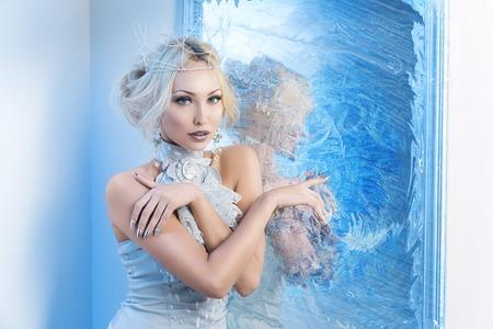 냉동 미러 근처 서 왕관과 실버 상단에 아름 다운 젊은 여자. 눈의 여왕. 공간을 복사합니다.