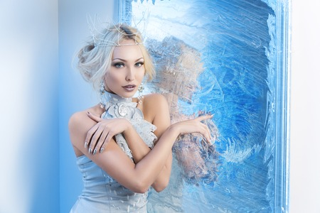 Beautiful young woman in crown and silver top standing near frozen mirror. Snow queen. Copy space.