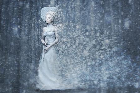 magie: Belle jeune femme. Fairy tale reine de neige en robe d'argent et la couronne avec le personnel dans la forêt magique. Copiez espace.