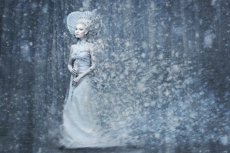 Beautiful young woman. Fairy tale snow queen in silver dress and crown with staff in magic forest. Copy space. Standard-Bild