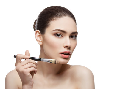 Beautiful young woman applying liquid foundation with brush. Isolated over white background. Copy space. Stock Photo