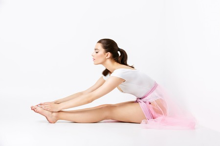 basque woman: Beautiful young woman in white bodysuit and pink basque stretching over white backgound. Copy space.