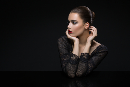 modelos desnudas: Beautiful young woman in lace top with red lips touching face. Over black background. Copy space.