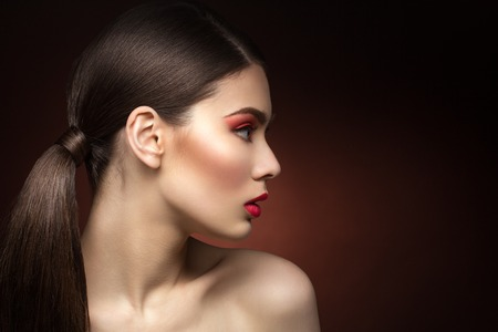 Closeup of young woman profile with red lips. Over dark background. Copy space.