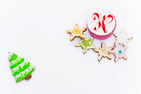 christmas candies: New Year cupcakes made in shape of snowman, deer and christmas candies. Over white background, Copy space